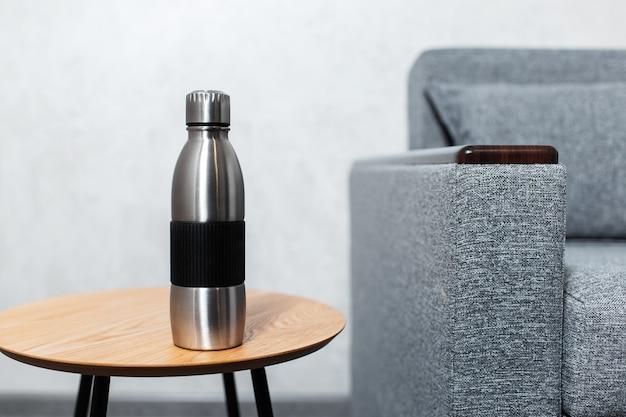 Zbliżenie: stalowa butelka termiczna wielokrotnego użytku na drewnianym stole przy szarej ścianie w pobliżu sofy.