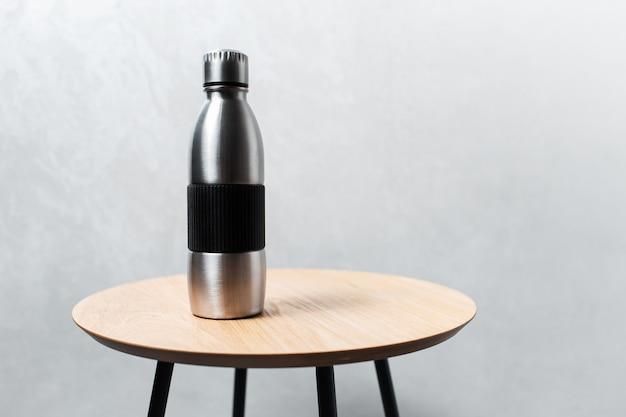 Zbliżenie: stalowa butelka termiczna wielokrotnego użytku na drewnianym stole.