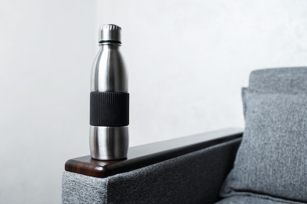 Zbliżenie: stalowa butelka termiczna wielokrotnego użytku na kanapie, na szarej ścianie.