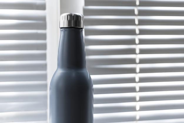 Zbliżenie: stalowa, ekologiczna butelka termiczna wielokrotnego użytku na tle okna z żaluzjami.