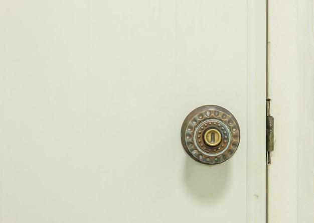 Zbliżenie stara klamka przy białych drzwiach toaleta