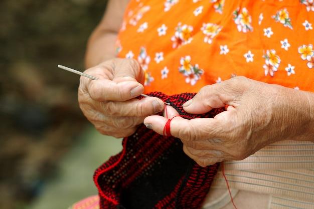 Zbliżenie stara kobieta w wsi, tajlandia dzianie robi handmade torbom w ona do domu.