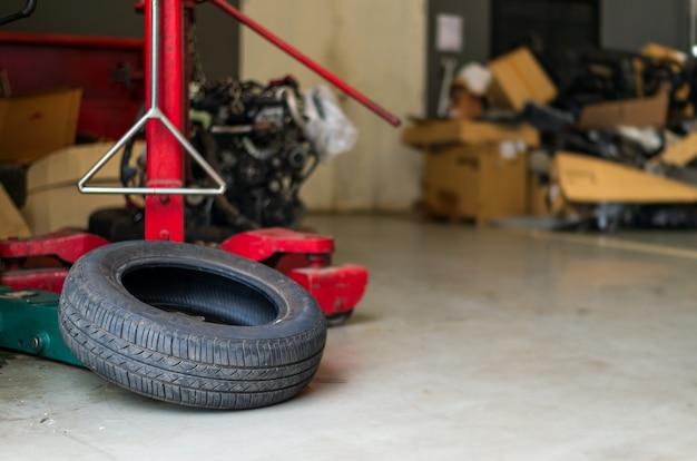 Zbliżenie stara opona w samochodowej naprawy staci z ostrością i lekkim w tle