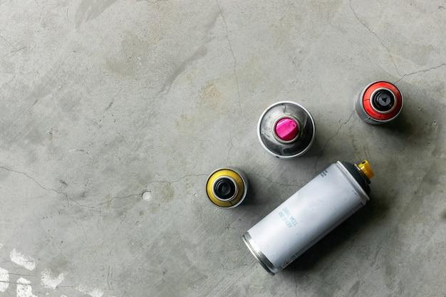Zbliżenie stare puszki farby w sprayu na cementowej podłodze