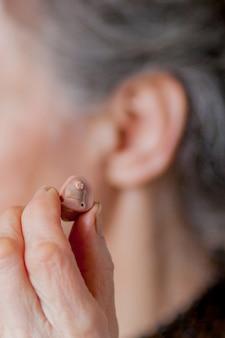 Zbliżenie starsza kobieta wkłada aparat słuchowego w jej ucho