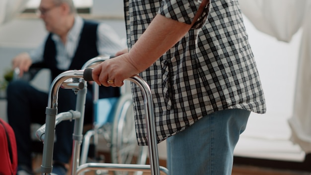Zbliżenie starszego pacjenta z niepełnosprawnością za pomocą ramy spacerowej