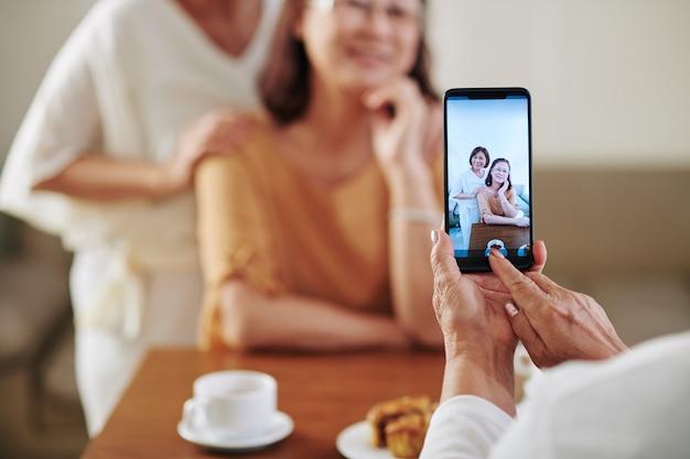 Zbliżenie starszej kobiety fotografującej przytulające się koleżanki na smartfonie