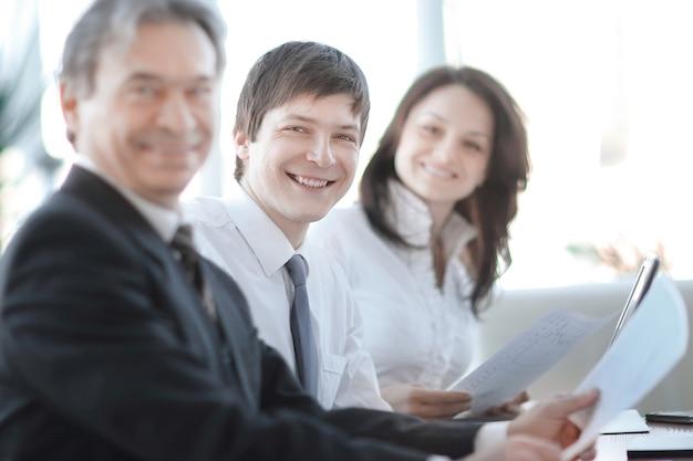 Zbliżenie. starszy biznesmen siedzi na spotkaniu. pojęcie pracy zespołowej