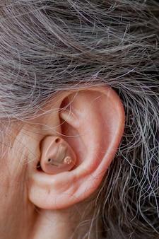 Zbliżenie starszy kobieta wkładając aparat słuchowy w uszy