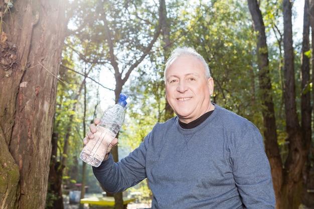 Zbliżenie starszy mężczyzna trzyma butelkę wody