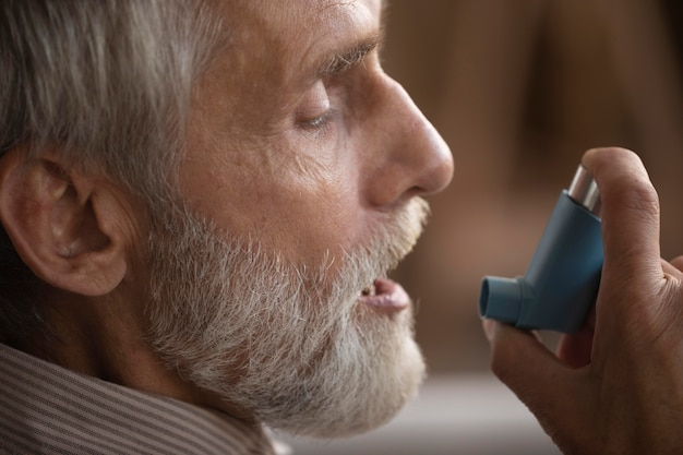 Zbliżenie starszy mężczyzna trzyma inhalator astmy