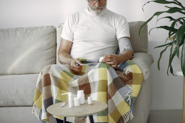 Zbliżenie starszy mężczyzna w wieku 70-75 lat pomiaru ciśnienia. mężczyzna do pomiaru ciśnienia krwi. zdrowie i opieka.