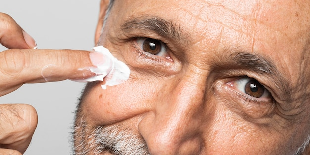 Zbliżenie starszy mężczyzna za pomocą kremu do twarzy