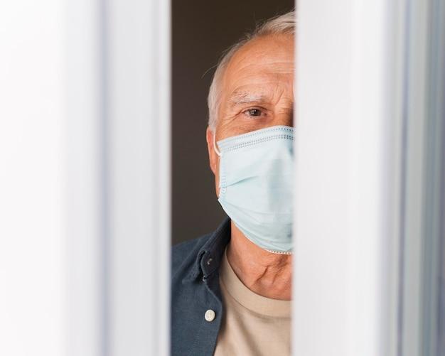Zbliżenie stary człowiek z maską w pomieszczeniu