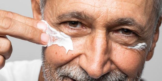 Zbliżenie stary człowiek za pomocą kremu do twarzy