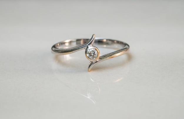 Zbliżenie stary diamentowy pierścionek na zamazanym marmurowym podłogowym tle