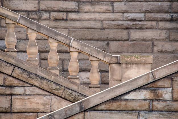 Zbliżenie starych klatek schodowych budynku z kamienia pod działaniem promieni słonecznych