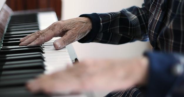 Zbliżenie starych kobiecych rąk z głębokimi zmarszczkami grającymi na pianinie stara babcia jest pianistą