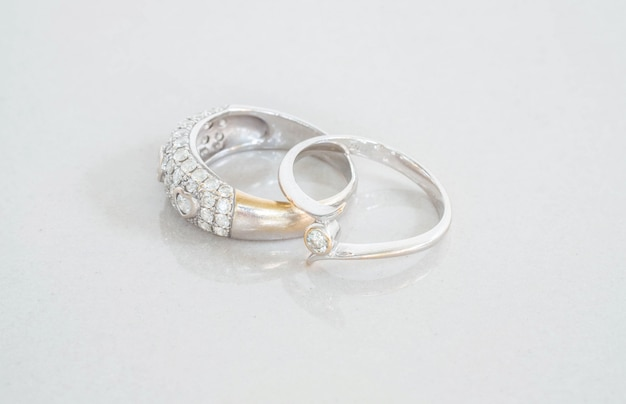 Zbliżenie starych pierścionków z brylantem na niewyraźne marmurowe podłogi kamienne tło