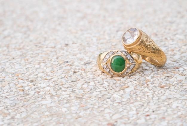 Zbliżenie starych pierścionków z brylantem na tło zamazane pole kamienne podłogi