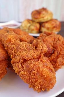 Zbliżenie sterty złotobrązowe chrupiące smażone kurczaki z rozmytymi herbatnikami w tle