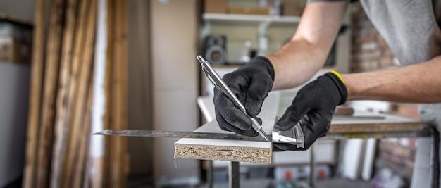 Zbliżenie stolarza trzymającego linijkę i ołówek podczas robienia znaków na drewnie przy stole w warsztacie.