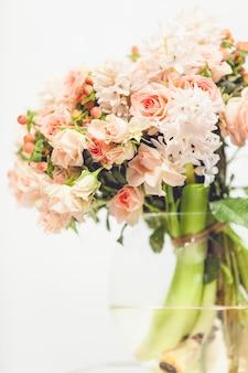 Zbliżenie stonowane zdjęcie małych różowych kwiatów w szklanym wazonie