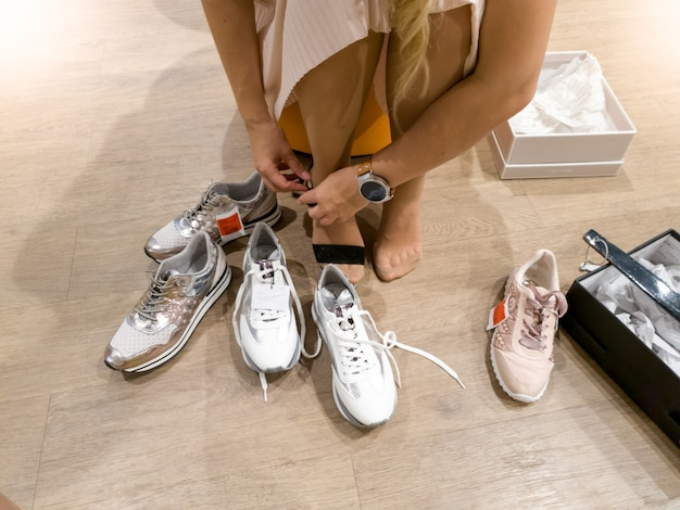 Zbliżenie stonowanych obraz młodej kobiety przymierza nowe trampki podczas robienia zakupów