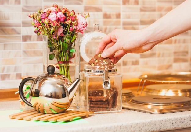 Zbliżenie stonowanych strzał człowieka biorącego ciasteczka ze szklanego słoika w kuchni