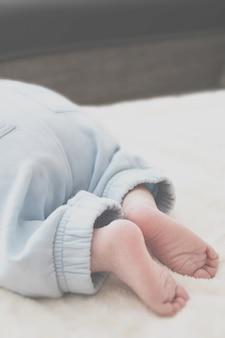 Zbliżenie stóp dziecka na białym kocem