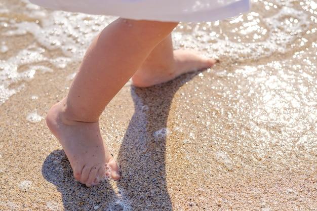 Zbliżenie stóp dziecka na piasku plaży morskiej w wodzie morskiej