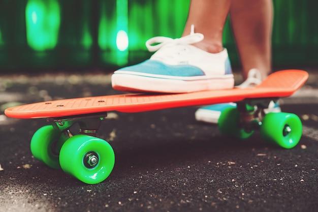 Zbliżenie stóp dziewczyn trampki jeździ na deskorolce pomarańczowy grosza na asfalcie