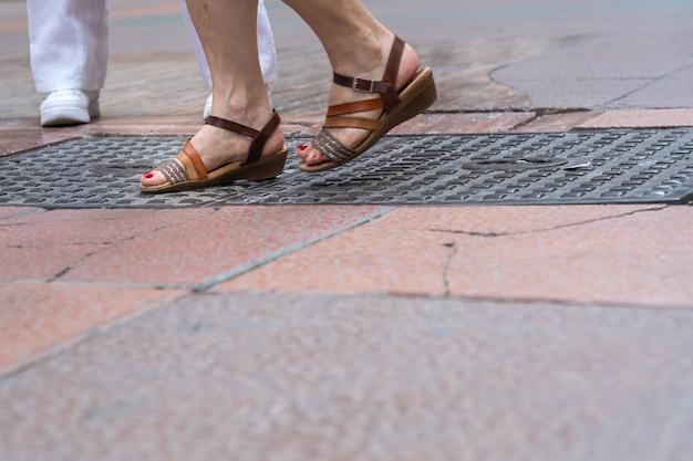 Zbliżenie stóp ludzi chodzących na ulicy handlowej ..
