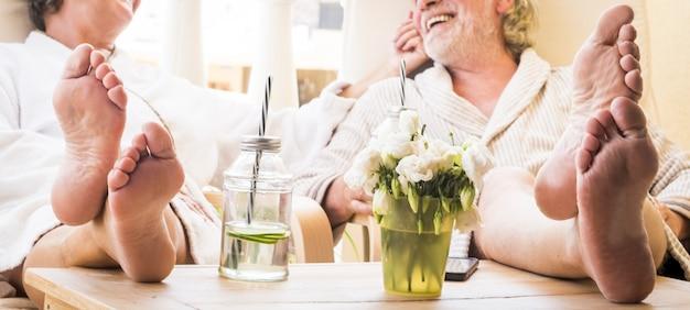 Zbliżenie stóp para seniorów na bajce w hotelu lub w domu przy koktajlu lub drinku - zdrowy i wspaniały styl życia - ciesząc się razem siedząc w domu