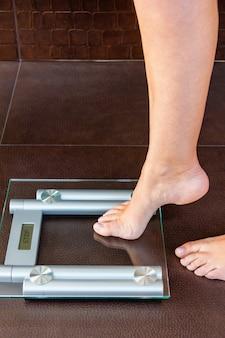 Zbliżenie stopy kobiety przesyłanie do wagi łazienkowej. koncepcja zdrowia i wagi