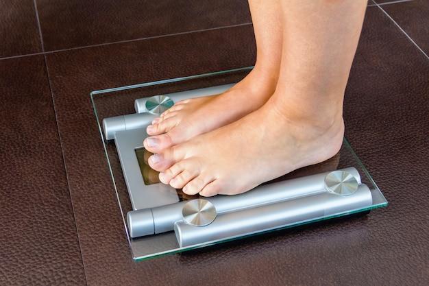 Zbliżenie stopy kobiety stojącej na wadze łazienkowej. pojęcie zdrowia i wagi.