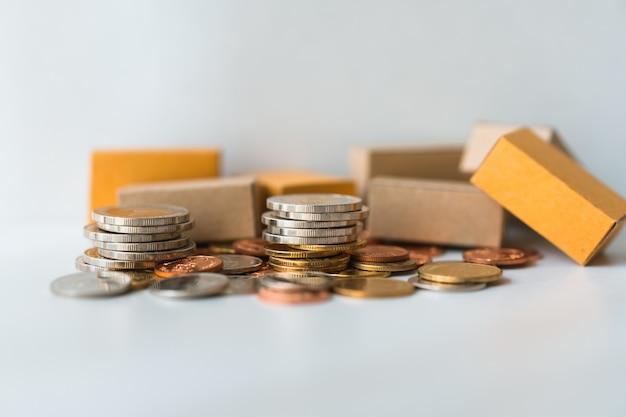 Zbliżenie stos monet i kartonów używać jako biznesu i logistyki pojęcie