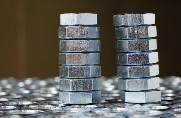 Zbliżenie stosu chromowanych metalowych nakrętek stojących na leżących orzechach w postaci plastrów miodu
