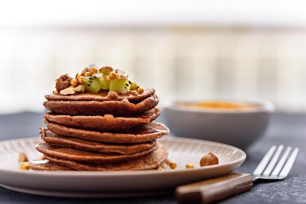 Zbliżenie stosu czekoladowe naleśniki z kiwi, orzechami laskowymi, syropem klonowym na talerzu z widelcem na kuchennym stole
