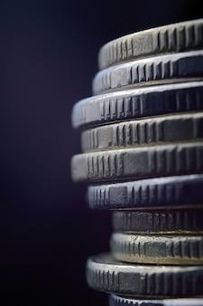 Zbliżenie stosu monet na białym tle na czarnym tle
