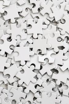 Zbliżenie stosu niekompletnych elementów białej układanki.