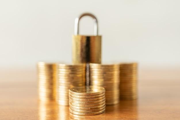 Zbliżenie stosu złotych monet ze złotym zamkiem na klucz główny na górze jako tło