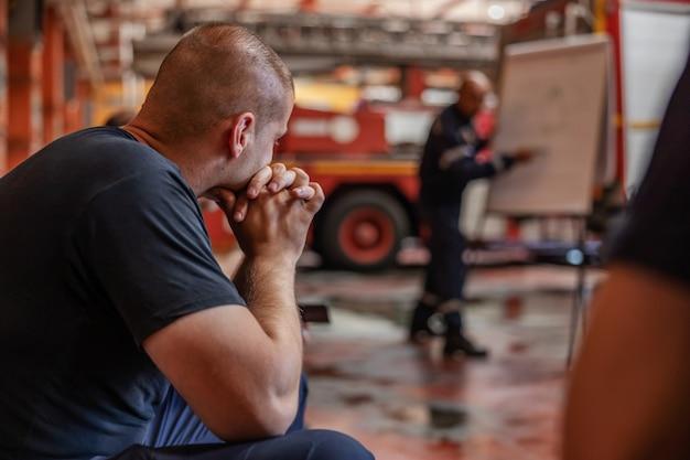 Zbliżenie strażaka siedzącego i słuchającego szefa, który mówi o taktyce, jak mają zamiar ugasić pożar. wnętrze straży pożarnej.