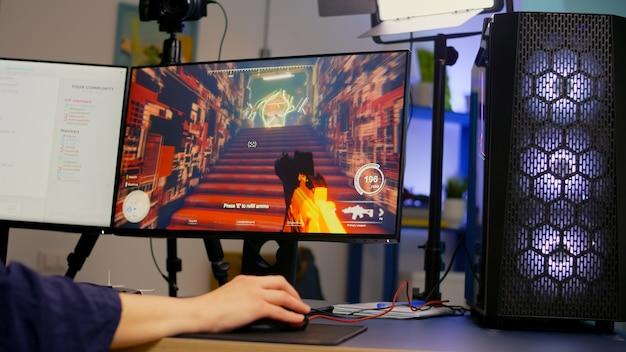 Zbliżenie streamera grającego w strzelankę pierwszoosobową za pomocą klawiatury i myszy rgb