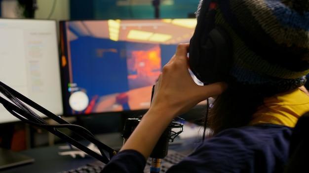 Zbliżenie streamera noszącego profesjonalne słuchawki do gier i grającego w gry wideo fps