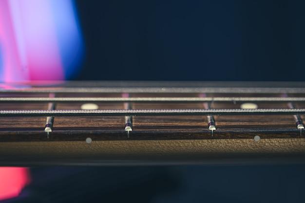 Zbliżenie strun na gryfie gitary basowej na niewyraźnym ciemnym tle.