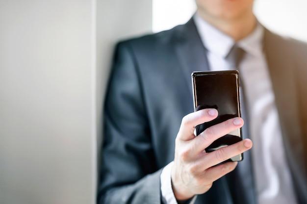 Zbliżenie strzał biznesmen używa smartphone przy biurem