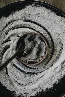 Zbliżenie strzał ceramiczny garnek do gotowania ze składnikami i łyżką w nim z mąką wokół