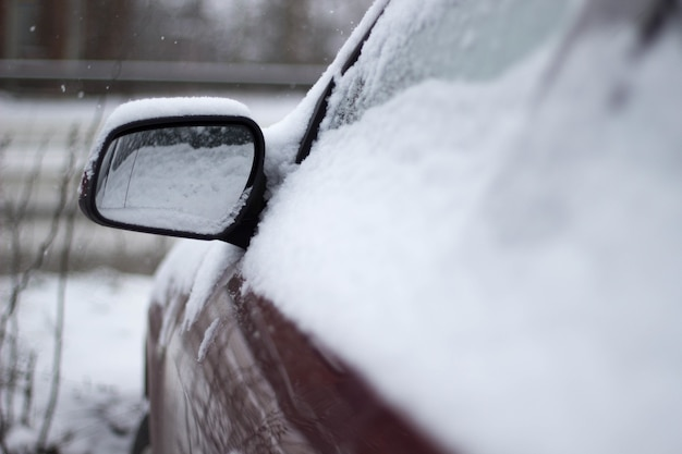 Zbliżenie strzał czerwonego samochodu pokrytego śniegiem