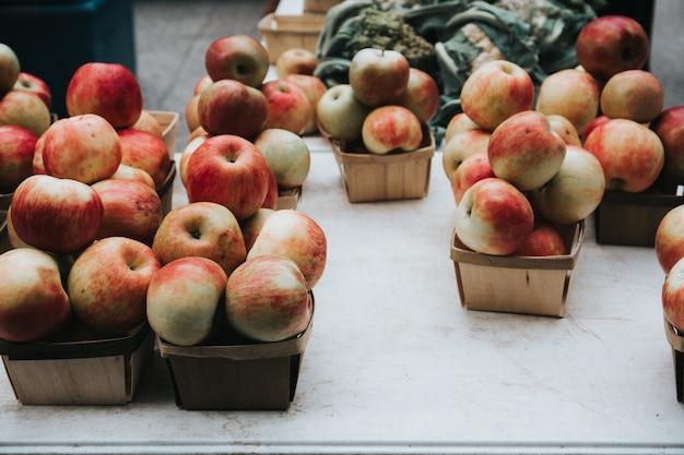 Zbliżenie strzał czerwoni jabłka w małych koszach w rynku